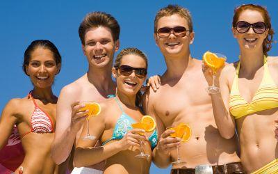 Junge Leute in Badesachen mit Cocktails