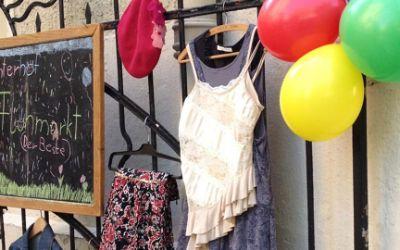 Hinterhofflohmarkt mit Luftballons, Kleidung und Tafel