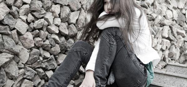Trauriges Mädchen sitzt auf einer Treppe