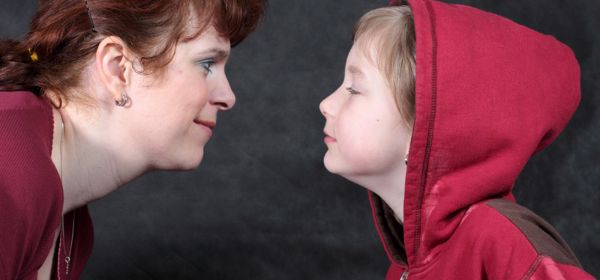 Mutter und Tochter schauen sich verschmitzt an