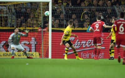 Dortmunds Torhüter Roman Bürki (l) kann das 2:0 von Robert Lewandowski nicht verhindern.