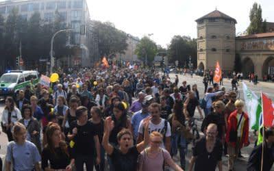 Teilnehmer einer Demonstration für bezahlbaren Wohnraum und gegen soziale Ausgrenzung unter dem Motto #ausspekuliert ziehen mit einem Banner durch die Stadt und gehen am Isartor (r) vorbei.