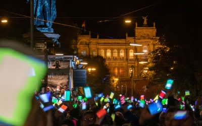 """Zahlreiche Menschen demonstrieren vor dem Landtag gegen Rassismus und bilden mit ihren Smartphones eine bunte """"Lichterkette""""."""