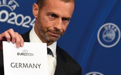 """Aleksander Ceferin, Präsident der UEFA, zeigt während der Bekanntgabe-Zeremonie zur Ausrichtung der Fußball-Europameisterschaft 2024 ein Blatt mit der Aufschrift """"""""Germany""""."""