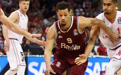 Jared Cunningham (M) von München spielt den Ball, Luka Mitrovic (l) und Maodo Lo (r) von Bamberg verteidigen.