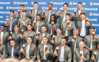 Das Team des FC Bayern München sitzt in Lederhosen bei einem Fototermin in einer Brauerei