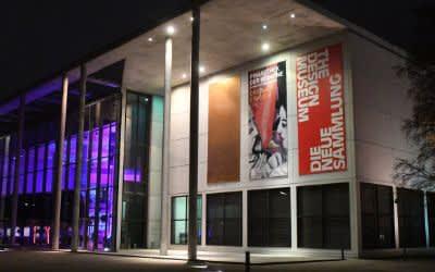 Die Pinakothek der Moderne ist am Abend von außen beleuchtet.