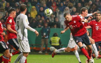 Simon Engelmann (4.v.l) aus Rödinghausen blickt auf Niklas Süle (4.v.r) aus München, der den Ball wegköpft.