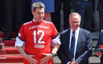 Ministerpräsident Markus Söder (l.) zieht ein neues Heimtrikot des FC Bayern an.