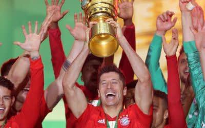 Bayerns Doppel-Torschütze Robert Lewandowski (M.) stemmt den DFB-Pokal in den Berliner Nachthimmel