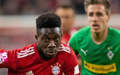 Bayerns Alphonso Davies und Gladbachs Patrick Herrmann (l-r.) bemühen sich um den Ball.
