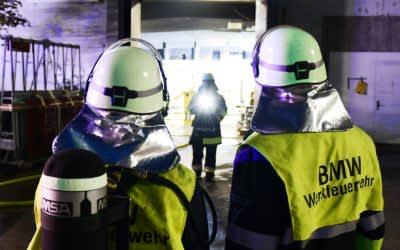 Einsatzkräfte der BMW-Werksfeuerwehr stehen vor einer Halle auf dem Werksgelände.