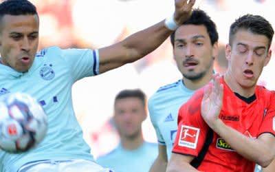 Thiago (l) und Freiburgs Janik Haberer im Zweikampf um den Ball.