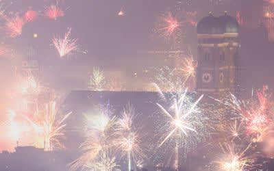 01.01.2019, München: Feuerwerksraketen explodieren in der Silvesternacht über der Frauenkirche und der Innenstadt