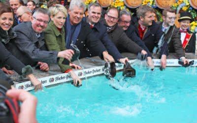 Oberbürgermeister Dieter Reiter (4.v.l.) und wichtige Stadtvertreter beim Geldbeutelwaschen am Fischbrunnen