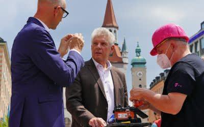 Timotheus Höttges (l) erklärt Dieter Reiter die Glasfasertechnik.