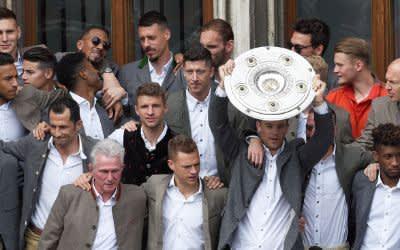 Die Mannschaft des FC Bayern München mit Torwart Manuel Neuer hält bei der Meisterfeier auf dem Rathausbalkon die Meisterschale in der Hand.