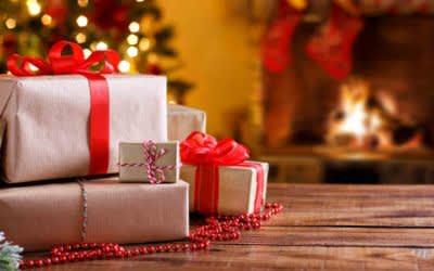 Geschenke auf einem Holztisch vor Christbaum und Kamin