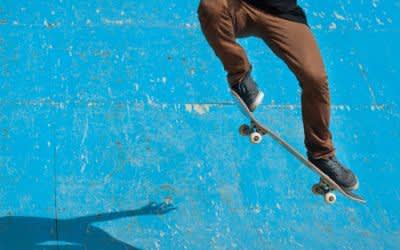Skateboarder macht Kickflip vor blauer Wand