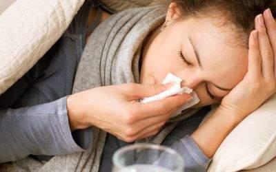 Frau liegt mit Grippe im Bett