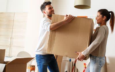 Eine Frau und ein Mann tragen eine Umzugskiste