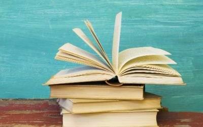 Aufgeschlagenes Buch auf Stapel