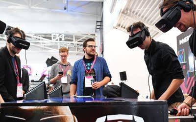 Teilnehmer der Medientage spielen mit VR-Brillen am Tischkicker