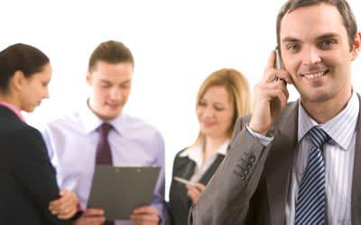 Mann mit Handy telefoniert vor einer Gruppe anderer Büroangestellter