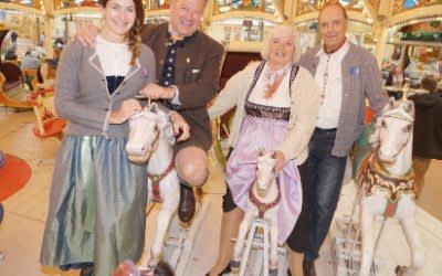 Natalie Schmid und Wiesn-Chef Josef Schmid auf Karrussel mit den Senioren Sonja Engelbrecht (65) und Horst Rauwolf (76).