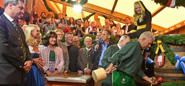 Markus Söder (l-r, CSU), Ministerpräsident von Bayern, und seine Frau Karin Baumüller-Söder schauen Dieter Reiter (SPD), Oberbürgermeister von München beim traditionellen Fassanstich zu.