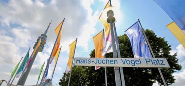 Das neue Schild mit dem Namen des Hans-Jochen-Vogel-Platzes vor Fahnen und dem Olympiaturm