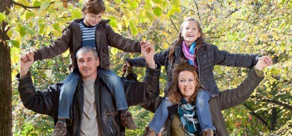 Familie mit Kindern auf den Schultern der Eltern