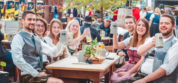 Menschen am Tisch im Airbräu erheben ihre Krüge