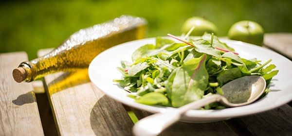 Salat und Olivenöl auf Holztisch