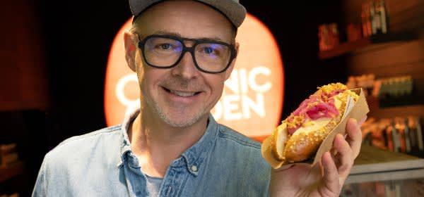 Holger Stromberg mit einem Hot Dog des Organic Garden Signature Stores