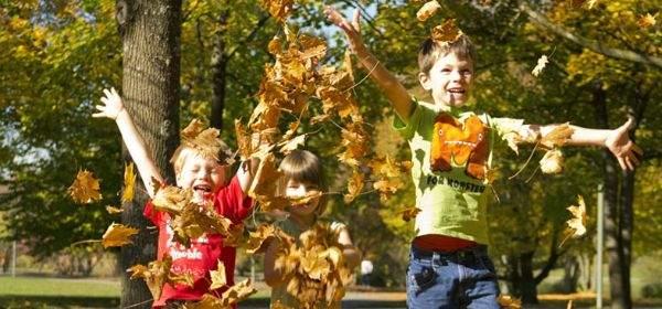Kinder spielen und springen im Herbstlaub