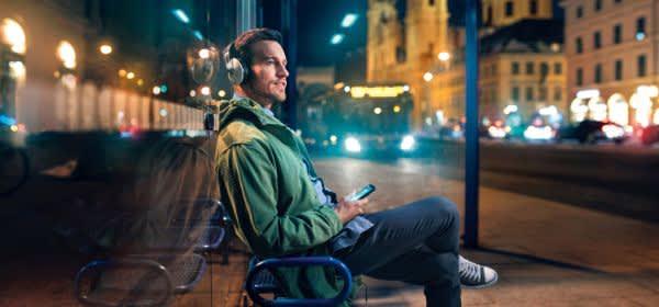 Mann mit Kopfhörern an einer Bushaltestelle