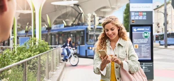 Frau an einer Haltestelle schaut aufs Handy
