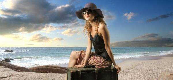 Frau mit Hut sitzt am Strand auf ihrem Koffer