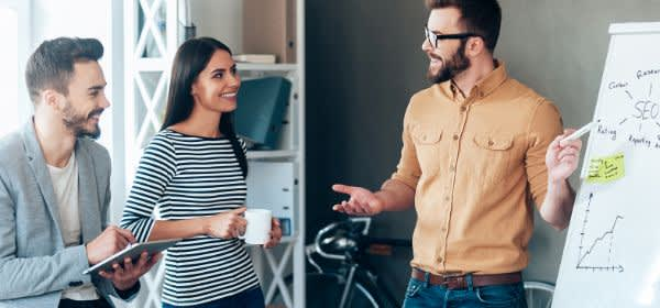 Angestellte diskutieren gutgelaunt vor Flipchart