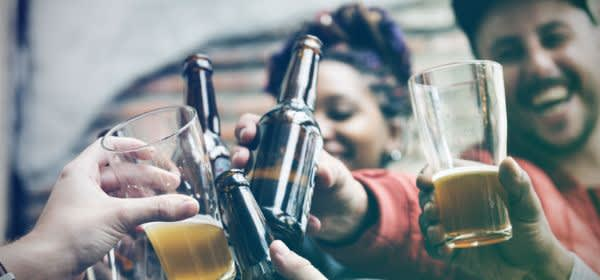Junge Leute stoßen mit Bier an