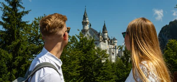 Mann und Frau schauen auf Schloss Neuschwanstein