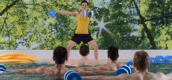 Aquafitness-Kurs: Frau animiert Kursteilnehmer