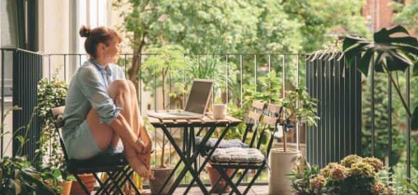 Frau sitzt auf dem Balkon vor einem Laptop