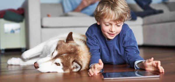 Kind mit Hund und Tablet auf dem Wohnzimmerboden