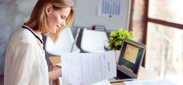 Junge Frau studiert Vertragsunterlagen