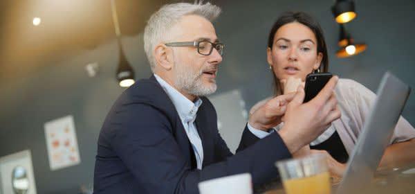 Geschäftsfrau und Geschäftsmann diskutieren vor Laptop