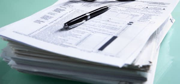 Stapel an Formularen, darauf eine Brille und ein Stift