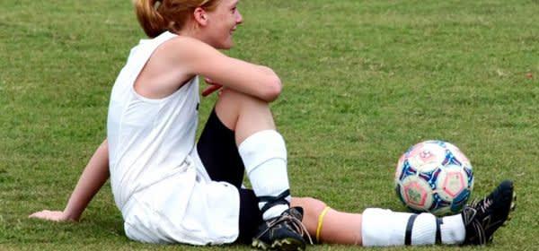 Mädchen dehnt sich neben Fußball
