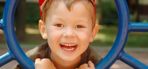 Kind auf Spielplatz steckt Kopf durch Gerüst
